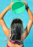 Water hair. A young girl pours water over her hair Royalty Free Stock Image