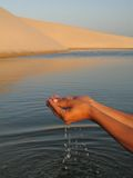 Water hand. Hand removing water of the lagoon between dunes Stock Photography