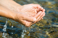 Water in the hands of Royalty Free Stock Photos