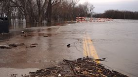 The Mississippi river floods the banks breaching levee closing roads