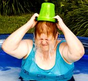 Water on the Head. Pouring a bucket of water on her head Stock Images