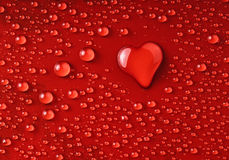 Water heart. Water drops on red surface forming a heart shape Royalty Free Stock Images
