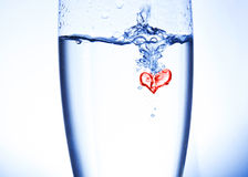 Water heart. Poring water into a glass, creating a heart in the bubbles. Taken in studio with a white background Royalty Free Stock Photos