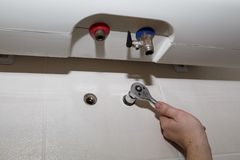 Water heater repairs. A man working with a ratchet wrench Stock Image