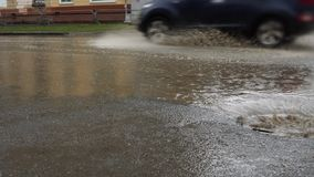 Rain falling on road, flowing through sewer drain. Cars drive on a flooded way. Water from heavy rain flows through a manhole cover into a storm drain. Splash stock footage