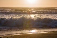 Water het bespatten op strandzonsondergang Stock Foto