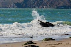 Water het bespatten in rots op strand Stock Afbeelding