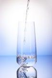 Water het gieten in één-derden volledig het drinken glas stock foto's