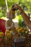 Water het gieten aan het witte standbeeld van Boedha, Songkran-festival stock foto's