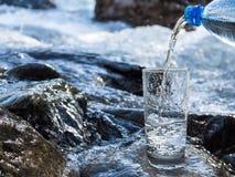 Water het gieten in een glas van fles Royalty-vrije Stock Fotografie