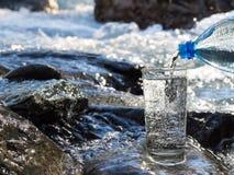 Water het gieten in een glas van fles Royalty-vrije Stock Foto's
