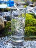 Water het gieten in een glas van fles Royalty-vrije Stock Afbeelding