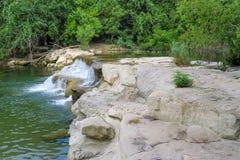 Water het gieten over afzettingsgesteente om een waterval te creëren Stock Afbeelding