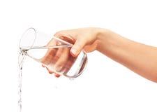 Water het gieten van volledig het drinken glas in de hand van de vrouw royalty-vrije stock afbeelding