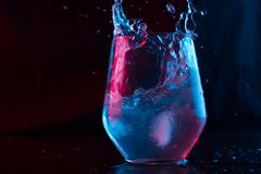 Water highlighted in blue and red splashing into a glass. Goblet on a black background stock photo