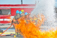 Water hitting fire with firemen. Firemen spraying water on a fire with fire truck in the background Stock Photography