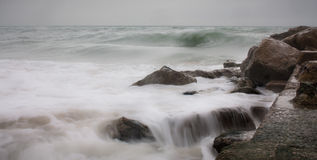 Water hitting rocks. Blurred water hitting rocks. Unsteady ocaen. Windy and cloudy weather Royalty Free Stock Photo