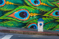 Water hose and blue green peacock feathers graffiti. San Francisco April 2015 Stock Photo