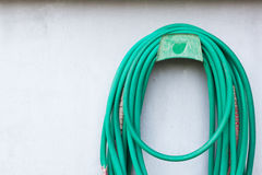 Water Hose with a bright wall. A green water hose with a bright wall Royalty Free Stock Photography