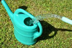 The water hose flows from the garden hose into the watering can. The water hose flows from the garden hose into the watering can stock images