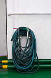 Water hose hanging on pipe Royalty Free Stock Photography