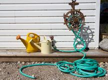 Water hose and watering cans Stock Photo