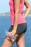 Water hydration detail. Detail of woman's arm and hand holding a bottle of water in front of the sea and coast. Healthy lifestyle concept Stock Images