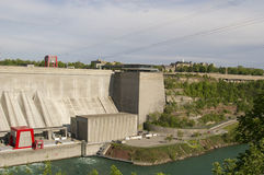 Water Hydro Dam at Niagara Falls. Concrete building and town and houses in background Royalty Free Stock Image