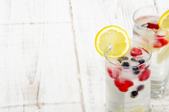 Water with  ice cubes - a refreshing drink. Mineral water with fruit frozen in ice cubes - a refreshing drink Stock Images