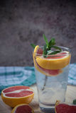 Water with ice, green mint and red orange in a glass Stock Image