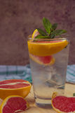 Water with ice, green mint and red orange in a glass. Beaker Royalty Free Stock Photography