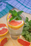 Water with ice, green mint and red orange in a glass. Beaker Stock Photo