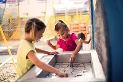 Water is important for the body. Two little girls playing with water in playground. Close up royalty free stock image