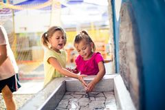 Water is important. Two little girls playing with water in playground. Close up Royalty Free Stock Images