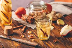 Water Infused with Pear, Cinnamon and Ginger. Glass of Water Infused with Sliced Pear, Cinnamon Stick, Ginger Root and Some Sugar. Ingredients Scattered on Royalty Free Stock Images