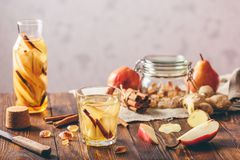Water Infused with Pear, Cinnamon, Ginger. Glass of Water Infused with Sliced Pear, Cinnamon Stick, Ginger Root and Some Sugar. Ingredients on Wooden Table and royalty free stock photo