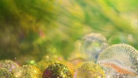 Water and ink mixing for a beautiful abstract. Glass balls with bubbles in the water stock footage