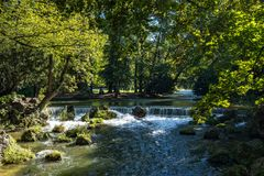 Water of the isar in The English Garden, Munich, Germany. Water of the isar spilling over rocks of green moss and surrounded with tall green trees, in The royalty free stock images