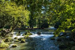 Water of the isar in The English Garden, Munich, Germany. Water of the isar spilling over rocks of green moss and surrounded with tall green trees, in The stock photography