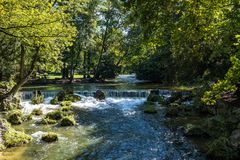 Water of the isar in The English Garden, Munich, Germany. Water of the isar spilling over rocks of green moss and surrounded with tall green trees, in The royalty free stock photos