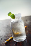 Water jar with a small plant and a straw Stock Photo
