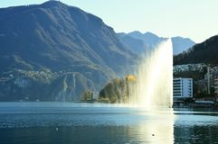 Water jet in Lake Lugano near the small town of Paradiso with mountains on the background and flare sun light, Lugano, Switzerland Royalty Free Stock Images