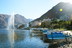 Water jet in Lake Lugano near the small town of Paradiso with mountains on the background and flare sun light, Lugano, Switzerland Royalty Free Stock Image