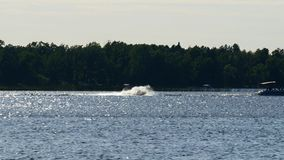 Water jet or personal water craft running fast and splashing the water. On a sunny day on a Minnesota lake stock video