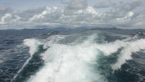 Water jet stream from a motor boat stern with cloudy sky and green mountain background