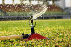 Water jets sprinkling stadium field Royalty Free Stock Image