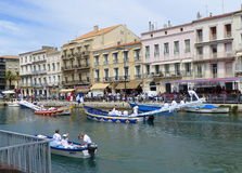 Water jousting competition and city buildings. Water jousting competition in the city of Sete, France stock images