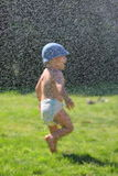 Water joys. Silhouette of baby enjoying a water spray Royalty Free Stock Photo
