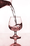 Water jug pouring to wine glass. On glass table Royalty Free Stock Photo