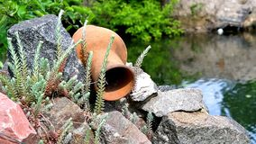 Water jug on the stones. Amphora, garden decoration with flowing water stock video footage